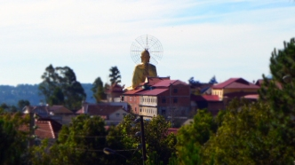 A giant golden Buddha, seen from a distance, overlooking Dalat and the surrounding hills.