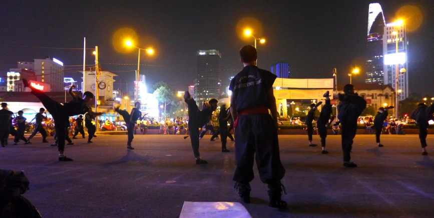 A martial arts class practices in a parking lot near Ben Thanh market.
