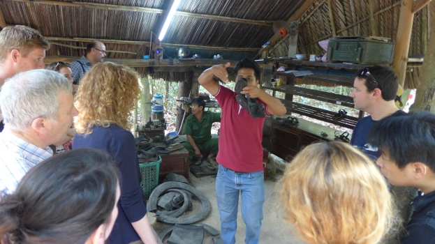 A tour guide explains how the Viet Cong would use recycled rubber to make sandals that were designed to obscure soldiers' tracks, just one example of the V.C.'s savvy.