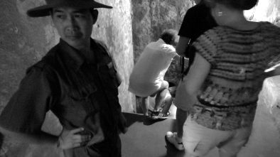 An attendant ushers tourists down into a Western-friendly mockup of the tunnels at Cu Chi. Though the mockup tunnels were built with Western dimensions in mind, down there cramped was an understatement (short video coming).